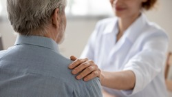 Close up young woman doctor touching senior patient shoulder at meeting in hospital, caring physician gp comforting and supporting mature man at medical appointment, psychological help concept