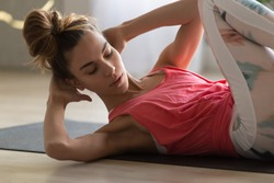Close up young woman doing crisscross exercise for abs lying on sports mat indoors, girl wearing sportswear makes bicycle crunches fitness working out at home, healthy active lifestyle routine concept