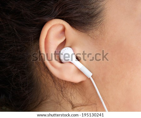 Close up young woman ear with earphone