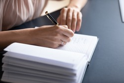 Close up young woman making notes in notebook, sitting at table. Female student listening to educational lecture, writing thesis in copybook. Successful businesswoman planning working day meetings.
