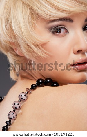Close up young woman portrait.  Beauty studio shoot. Healthy clean skin and perfect makeup on beautiful face of white model with short blonde hair.