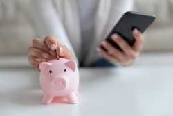 Close up young woman putting coin in little piggy bank while managing investments, family budget or medical insurance payments in mobile banking application, personal savings expenditures concept.