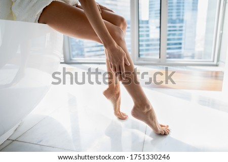 Close up young woman sitting on bath in modern bathroom with windows, touching legs, enjoying perfect smooth silky skin after epilation or home depilation procedure, applying moisturizing body cream Foto stock ©