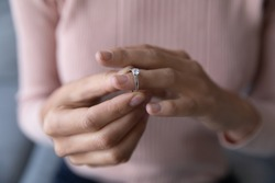 Close up young woman taking off wedding ring, divorce concept, female hands holding engagement ring, cheated girl break up with boyfriend or husband, family split, bad relationship