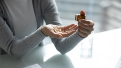 Close up young woman taking out pills from bottle, sitting at table with glass of water, preparing to take supplements or painkiller, emergency medicine, healthcare and treatment concept