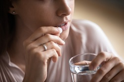 Close up young woman taking white round pill, holding water glass, unhealthy female taking painkiller to relieve headache, antidepressant or antibiotic medicine, emergency treatment