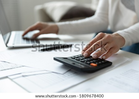 Close up young woman using calculator and computer software banking applications, managing monthly budget indoors, planning investment, loan payments, medical insurance or education expenditures.