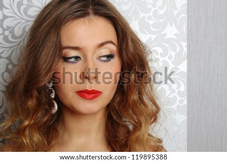 Close-up young woman with a crown. Makeup and hairstyle