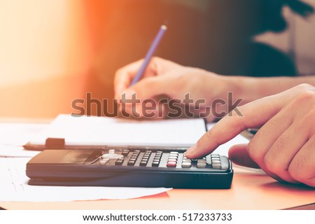 Close up young woman with calculator counting making notes at home, hand is writes in a notebook. Savings finances concept.