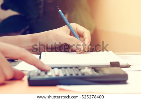 Close up young woman with calculator counting making notes at home, hand is writing in a notebook. Savings finances concept.