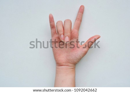 Close-ups of girl right sign language meaning I LOVE YOU and hand turn face up symbol isolated on a white background.