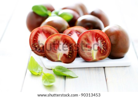 close-ups of  kumato tomatoes with fresh basil - fruits and vegetables