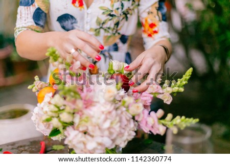 Close ups of woman florist's hands creating floral arrangements in garden #1142360774