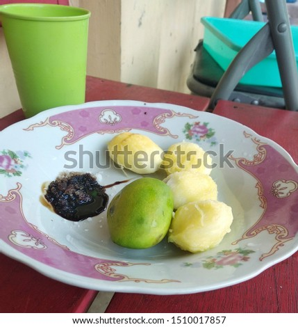 Close view image of half-ripe forest mangos, being served a salad in the antique plate. Small-sized, high vitamin C contained, yet only found in tropics, tropical rainforest.