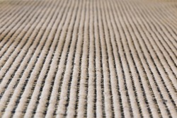 Close view of a black and white striped carpet. Macro and slanted perspective
