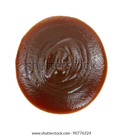 Close view of a blob of barbecue sauce on a white background.