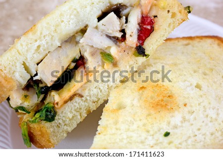 Close view of a chicken sandwich that has been cut in half on a small plate.