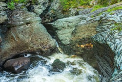 Close view of a creek in Sweden where the flushing water has eroded the slate rock