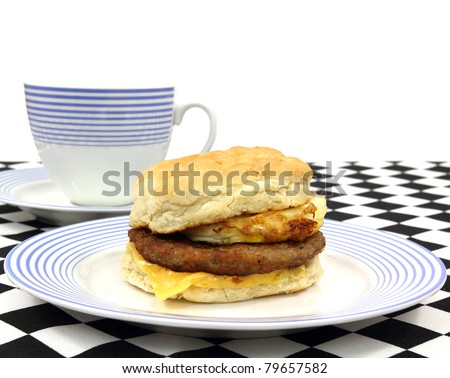 Close view of a freshly made sausage egg and cheese breakfast sandwich on a blue striped plate with coffee cup on a black and white checkerboard cloth.