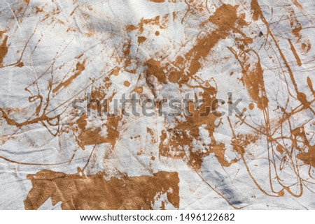 Close view of a muslin drop cloth with brown paint spills and splotches.