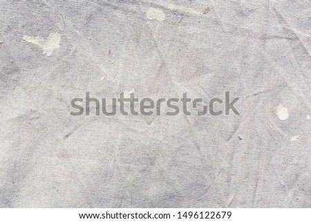 Close view of a muslin drop cloth with off white paint spills and splotches.