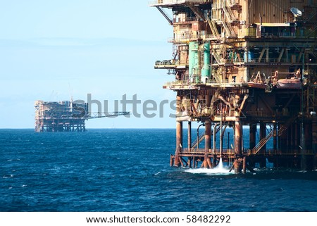close view of a oil rig with another far on horizon