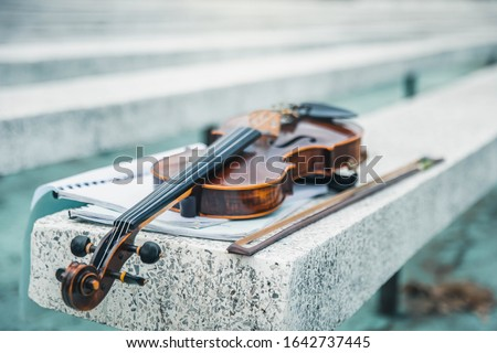 Close view of a violin strings and bridge. Violin in vintage style on outdood background. The violin on the table. Stock fotó ©