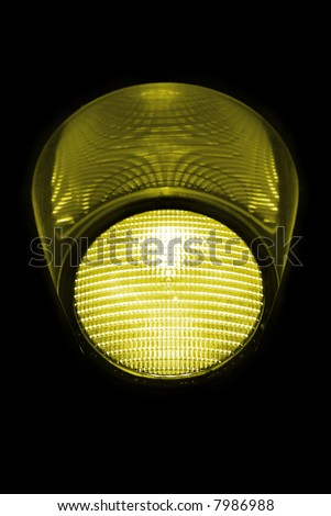 Close view of a yellow traffic light against a black background..