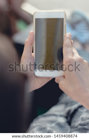 Close view of a young person holding and making use of a mobile phone or smart phone. Blurred background