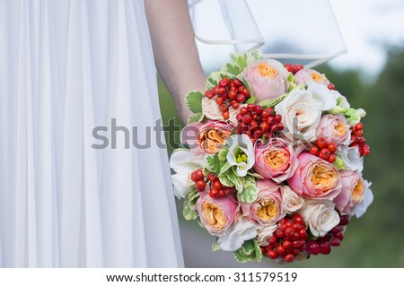 Close view of beautiful colorful wedding bouquet in a hand of a bride