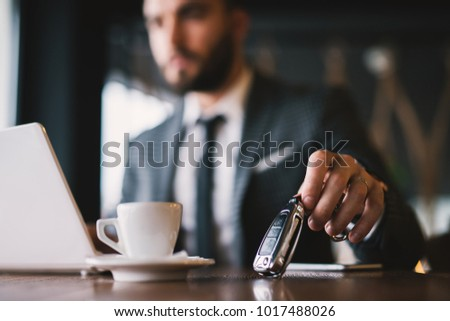 Close view of car keys put on the table next to cup of coffee by rich suited man in the cafe.