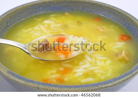 Close view of chicken with rice and vegetable soup and spoon