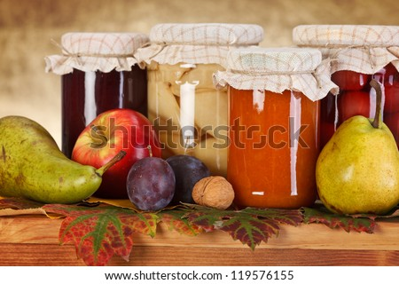 Close view of compotes and jam in glass bottle with fresh fruits - stock photo