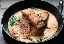 Close view of Creamy salmon or creamy tuscan salmon, salmon cooked with garlic bautter cream, spinach and tomato.
