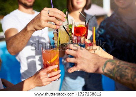 Close view of friends having fun at poolside summer party, clinking glasses with fresh summer cocktails near hotel swimming pool outdoors. People toast drinking juice at luxury villa on vacation. Stok fotoğraf ©