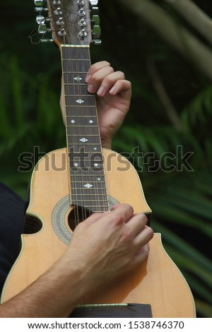 Close view of hands playing a cuatro; a Puerto Rico national music string instrument.