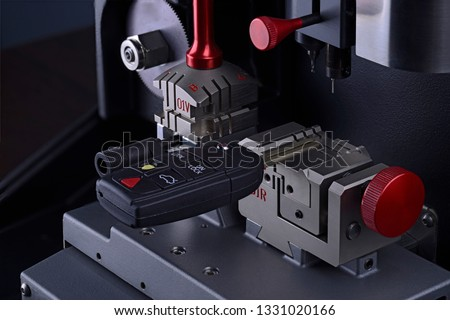 Close view of key copying machine with key. Duplicate machine make new key. Locksmith theme. Blank keys for cutting. Black modern car door opener.