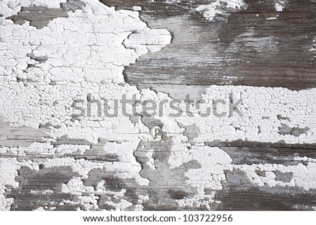 Close view of peeling white paint on boards.