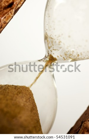 Close view of sand flowing isolated on white background. Focus is  down on the sand with reflection on hourglass.