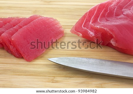 Close view of several pieces of yellowfin tuna sliced on wood cutting board with knife blade.