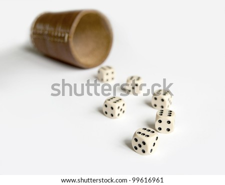 Close view of six dices with cup on white background. All dices got six eyes.