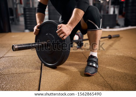 Close view of strong male hands of weightlifter fixing heavy metal weight discs of iron barbell, holding with effort, professional sport concept, selective shot