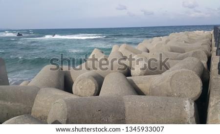 Close view of tetrapod stones on the sea shore to prevent coastal ersosion. Break water concrete tetrapods.