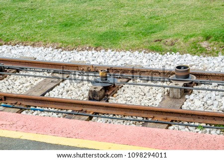 Close view of tram rail tracks showing the cable system which pulls the trams up to the Great Orme Mountain in LLandudno, Wales #1098294011
