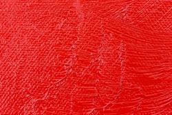 Close view of wet red paint on an artist canvas.