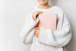 Close view of woman in white woolen sweater holding a book with empty pink cover in hands. Free space for your mock up of reading book concept background.