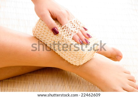 close view of woman scrubbing her leg in spa - stock photo