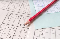 Close view on pencil on sudoku crosswords. Popular game with numbers.