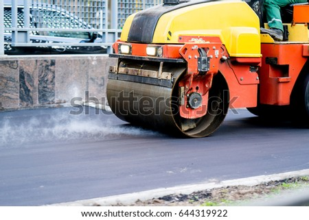 Close view on the road roller working on the new road construction site #644319922