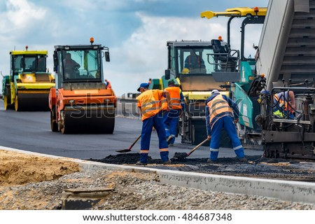 Close view on the workers and the asphalting machines stock photo